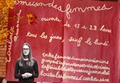 Affiche rouge de la maison des femmes de Toulouse, avec Justine Zeller devant