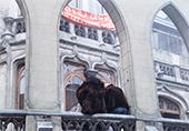 devant une église (qu'on devine) 2 femmes de dos, une banderole rouge sur l'église que l'on ne voit qu'en partie
