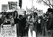 Manif du 1 mais 1976, femmes avec pancartes dont une en 1e plan Une femme sans homme c'est comme un poisson sans bicyclette