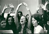 Mutualité mai 72 des femmes chantent certaines ont les bras au dessus de la tête avec le signe du MLF pouces qui se touchent des 2 mains et indexe (symbole du sexe des femmes)
