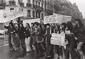 Manifestation du 8 mars 1975 des femmes se tiennent pas le bras et chantent, avec des pancartes
